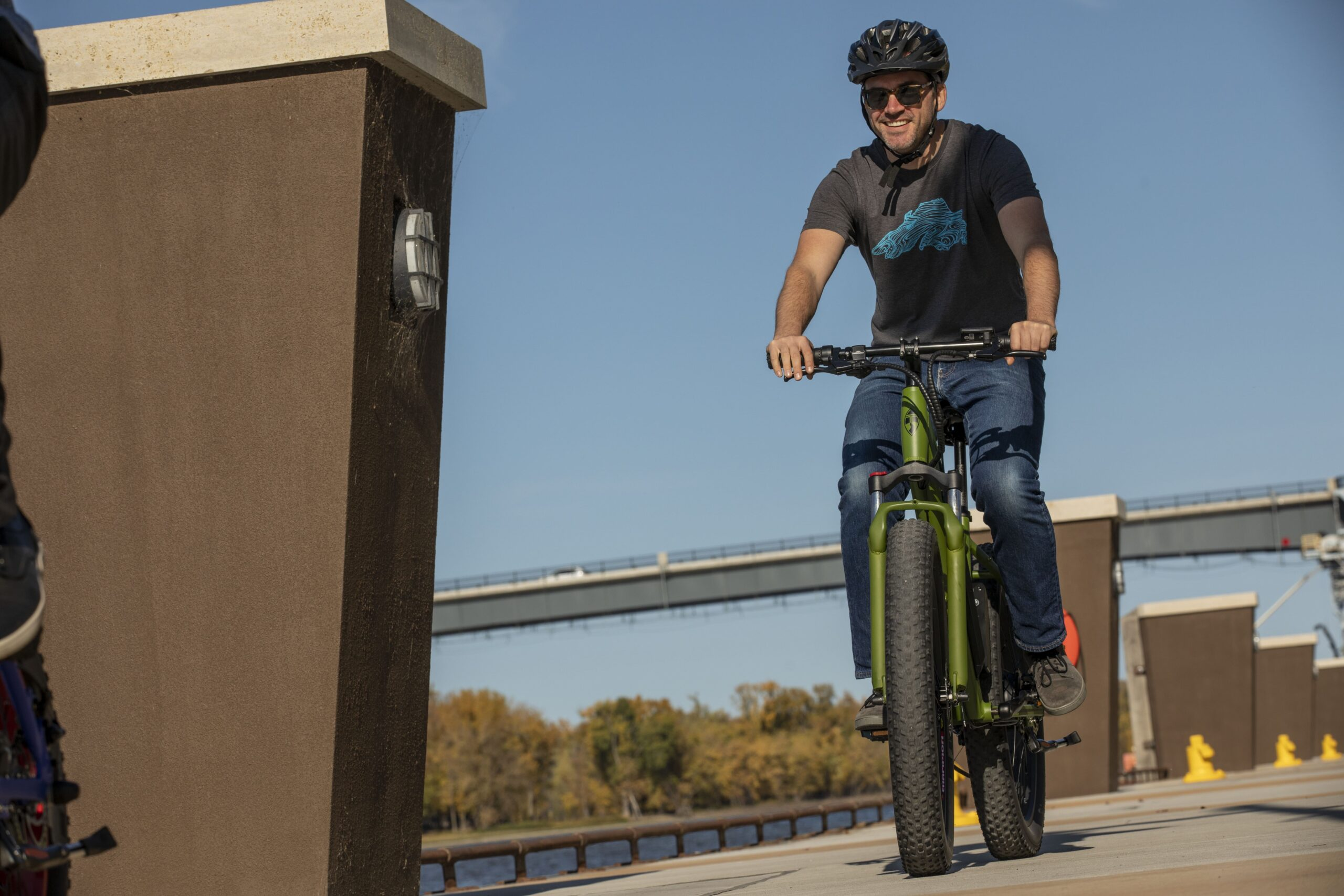 man riding green ebike on cement