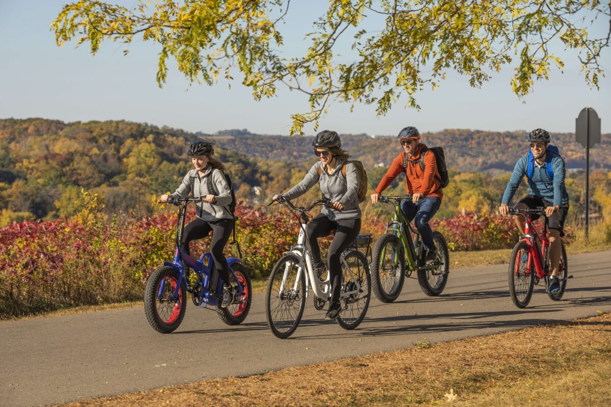 group of four people riding ebikes on bike trail