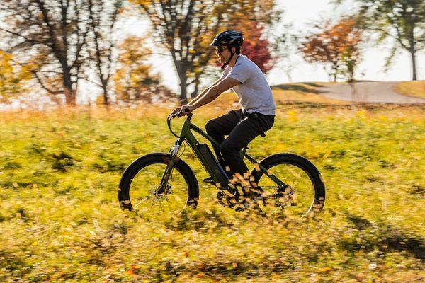 man riding bike through prairie field