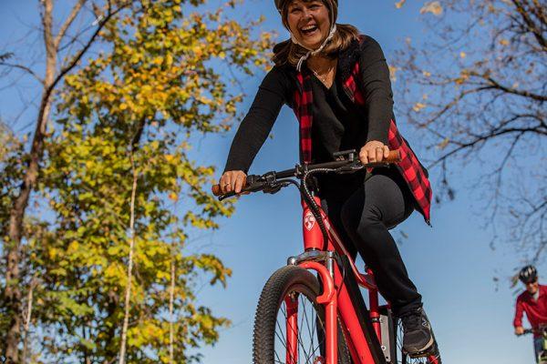 happy woman riding red bike