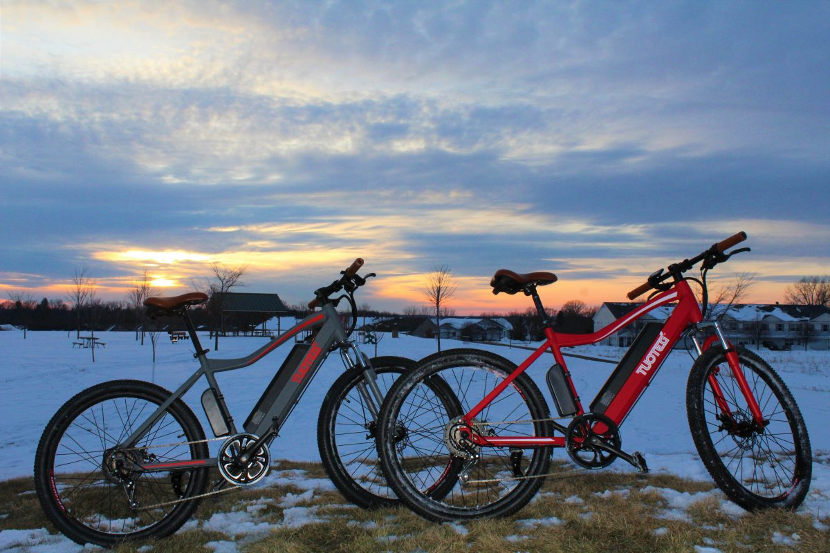 two bikes in front of snow and sunset