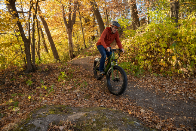 Man ebiking on trail in fall foliage