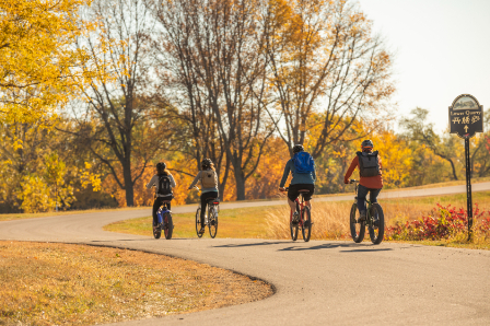 Four people riding an electric bike