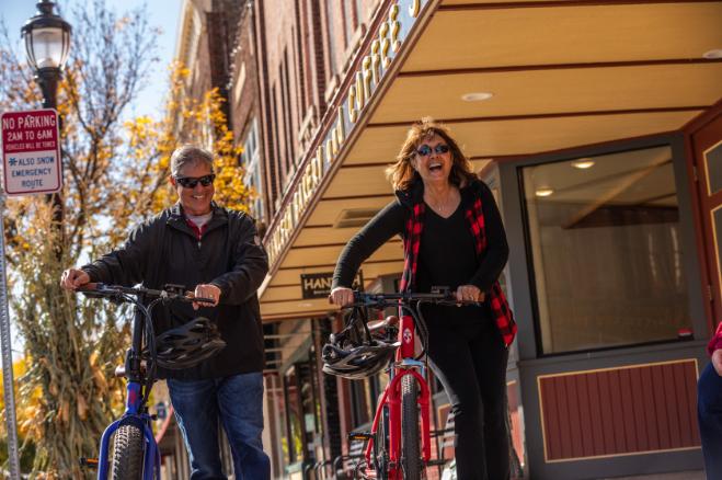 how long do batteries last on e bikes Couple walking with ebike outside