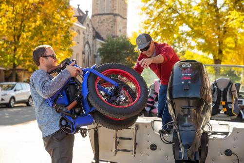 What is a Folding Electric Bike Men loading folding ebike into boat